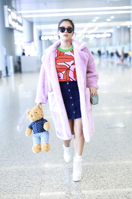 王菊身穿毛绒外套 手持布偶玩具亮相机场